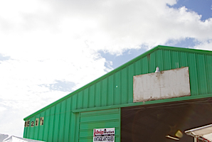 green flea market building with blue sky and clouds