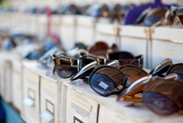 rows of sunglasses for sale at the flea market
