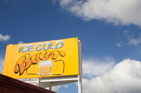 a sign for ice cold beer at the flea market with a bright blue cloudy sky behind it