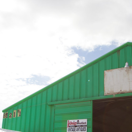 green flea market barn with blue cloudy sky